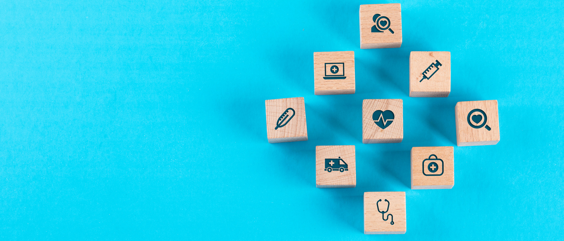 Medical check up concept with wooden blocks with icons on blue background flat lay. space for text. horizontal image